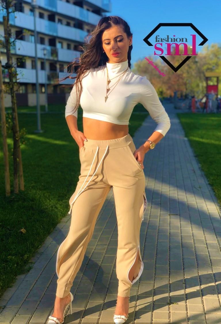 jasnobeżowe spodnie z wysokim stanem oraz zwężanymi nogawkami